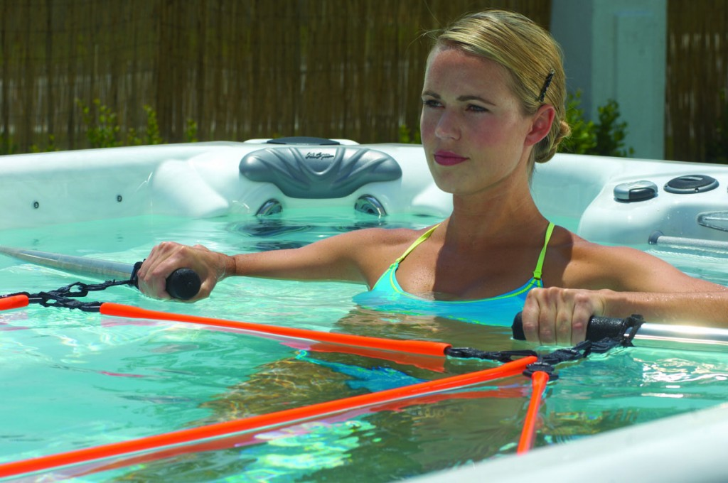 woman exercising with pulley system to row in Cal Spas swim spa Spa Brokers