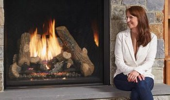 woman in white sweater sitting next to fireplace Spa Brokers Denver