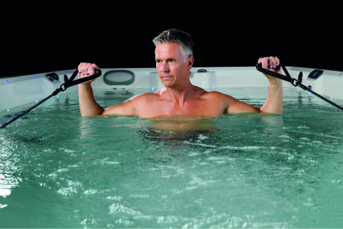 man using pully for arm exercise in swim spa denver spa brokers
